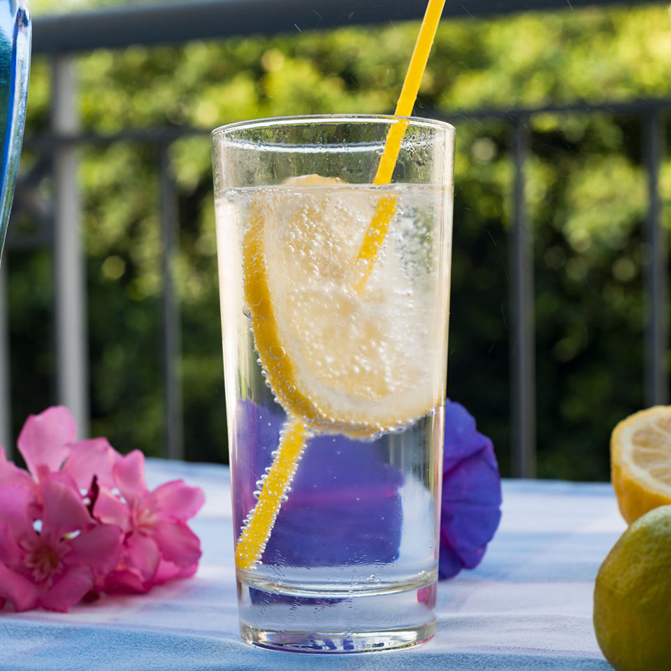 glass of sparkling water with a lemon and a straw