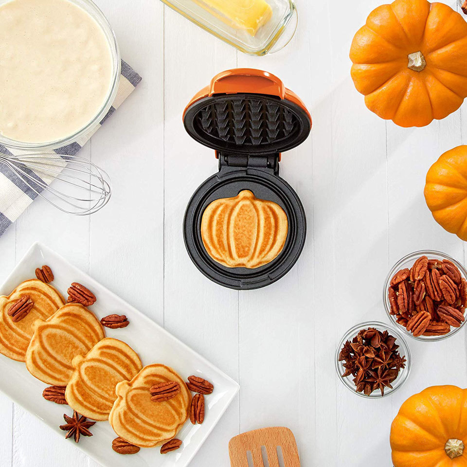 pumpkin waffle maker on a countertop with pumpkin shaped waffles and pecans on a serving plate