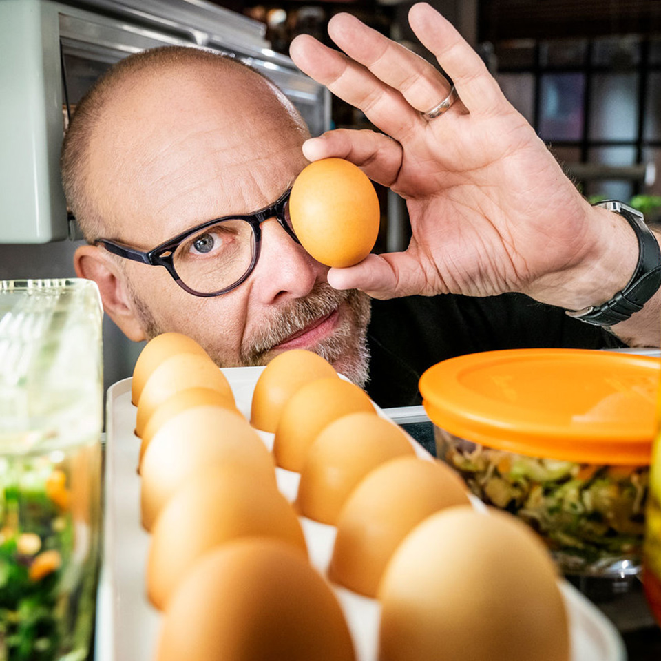 Alton Brown holding up egg while looking into a refrigerator