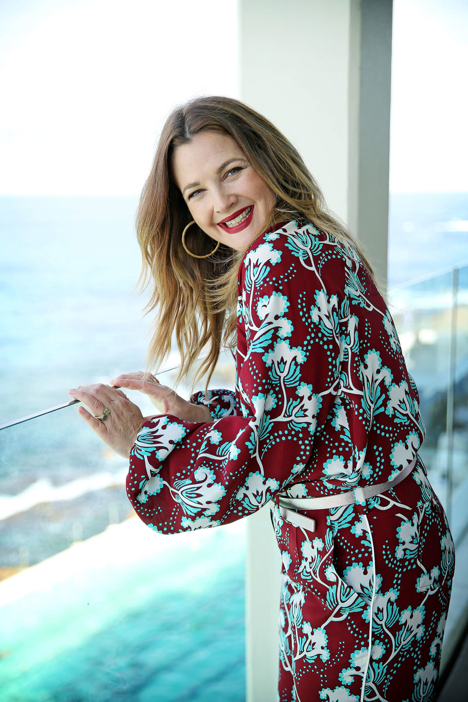 Drew Barrymore smiling while standing on a balcony overlooking the sea