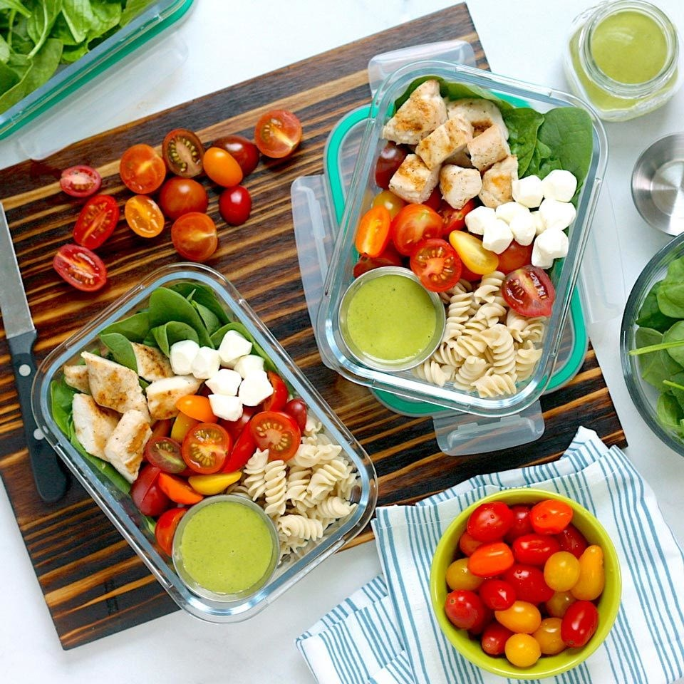 containers of salads with chicken, cheese, tomatoes and pasta