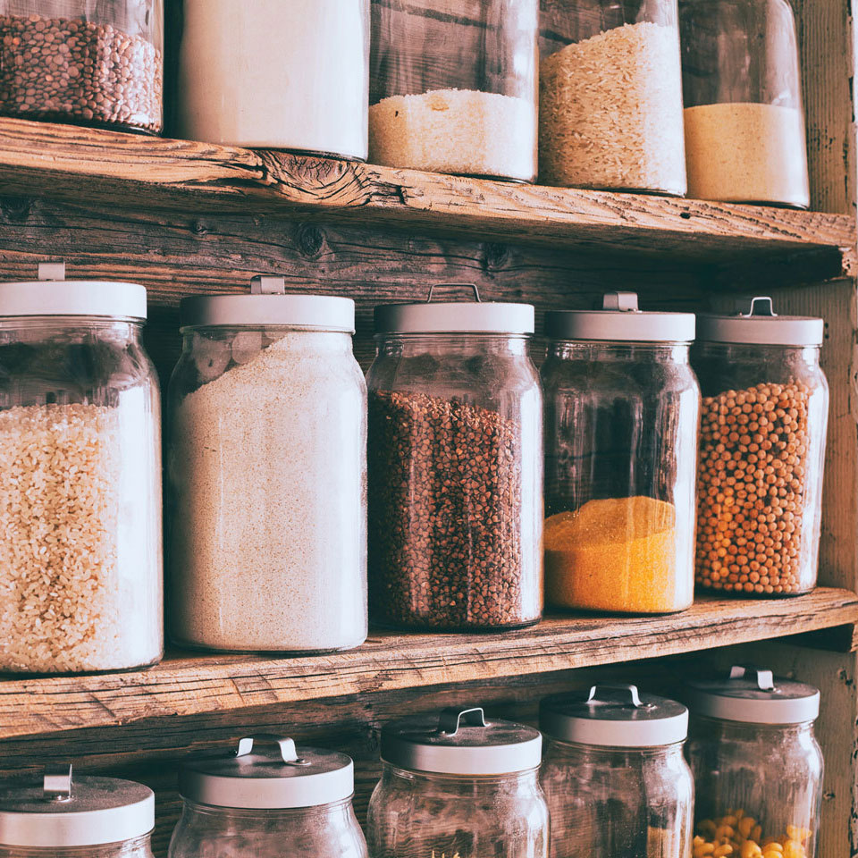 various spices and dried goods in glass jars on shelves