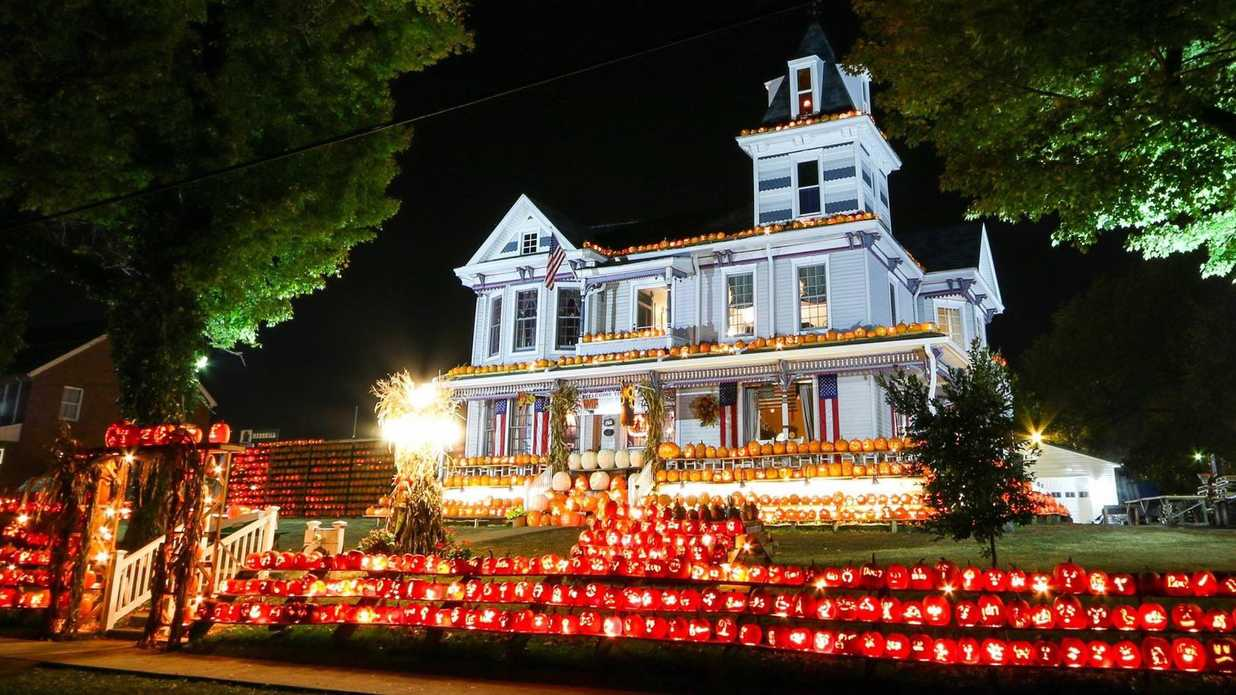 house decorated with thousands of pumpkins and jack-o-lanterns