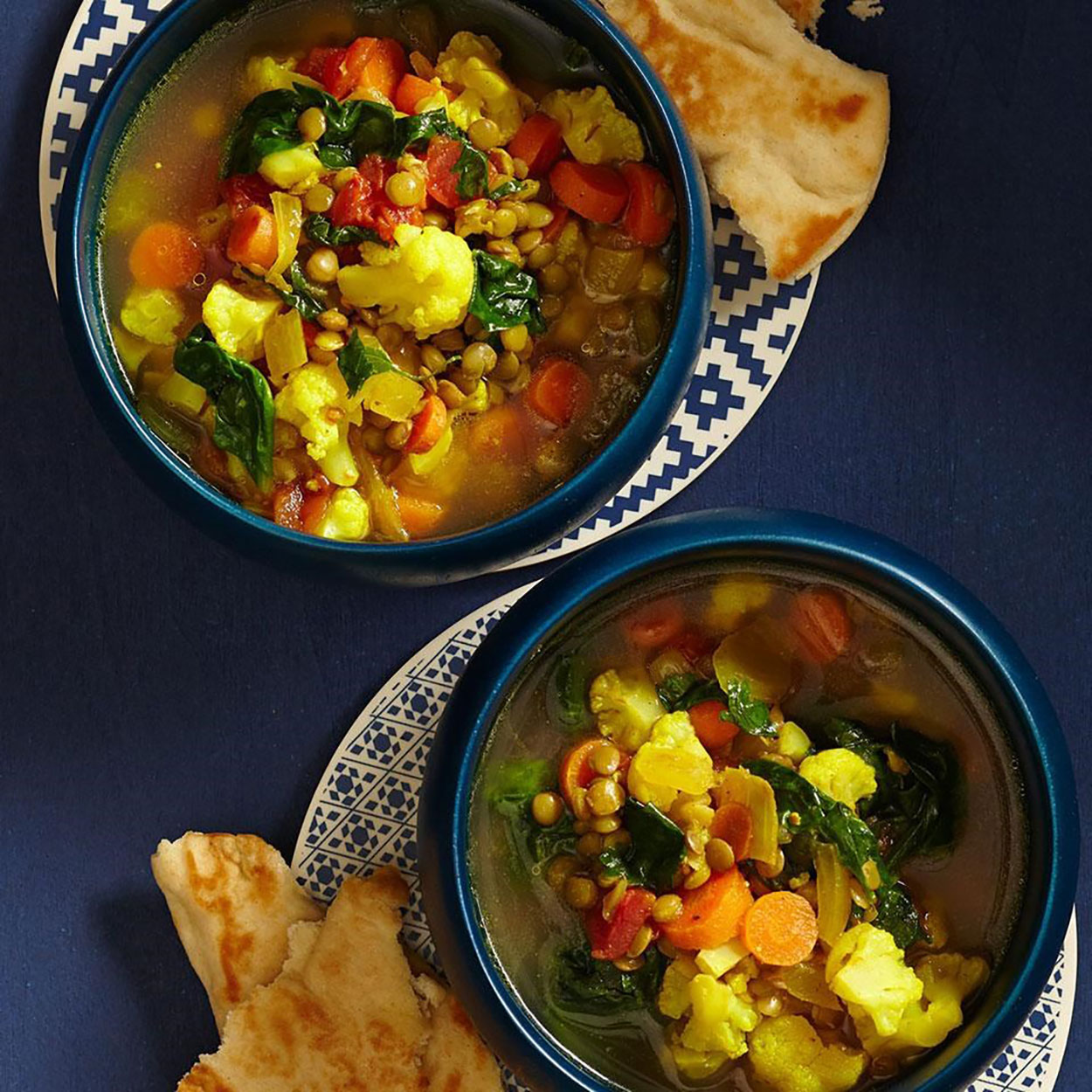 Slow-Cooker Moroccan Lentil Soup in bowls with flat bread