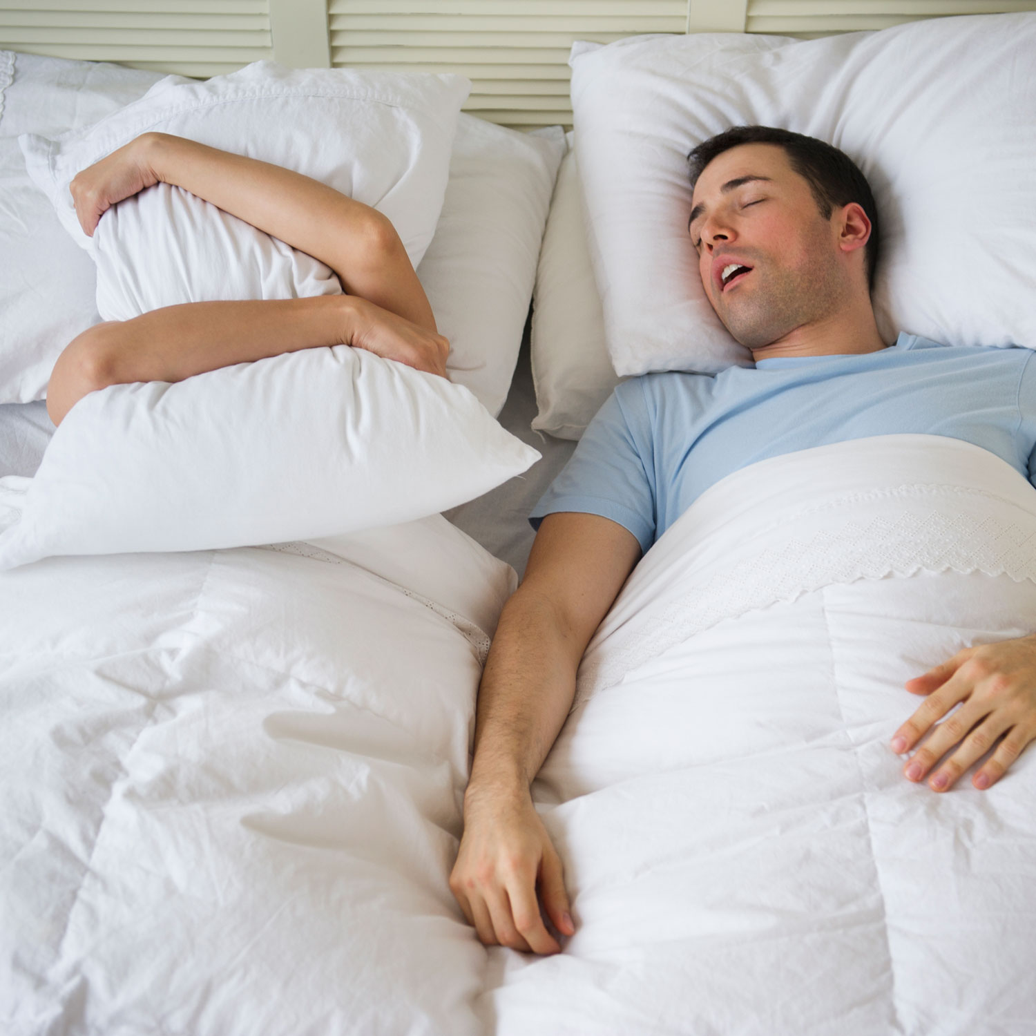 man and woman in bed - woman covering her face with pillow, man calmly sleeping