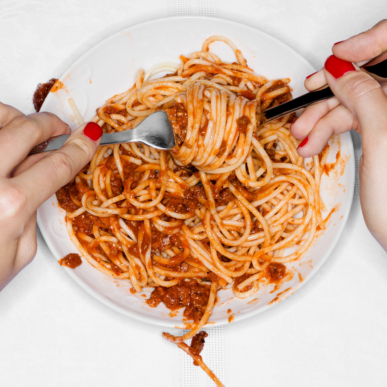 2 hands with utensils eating bowl of spaghetti