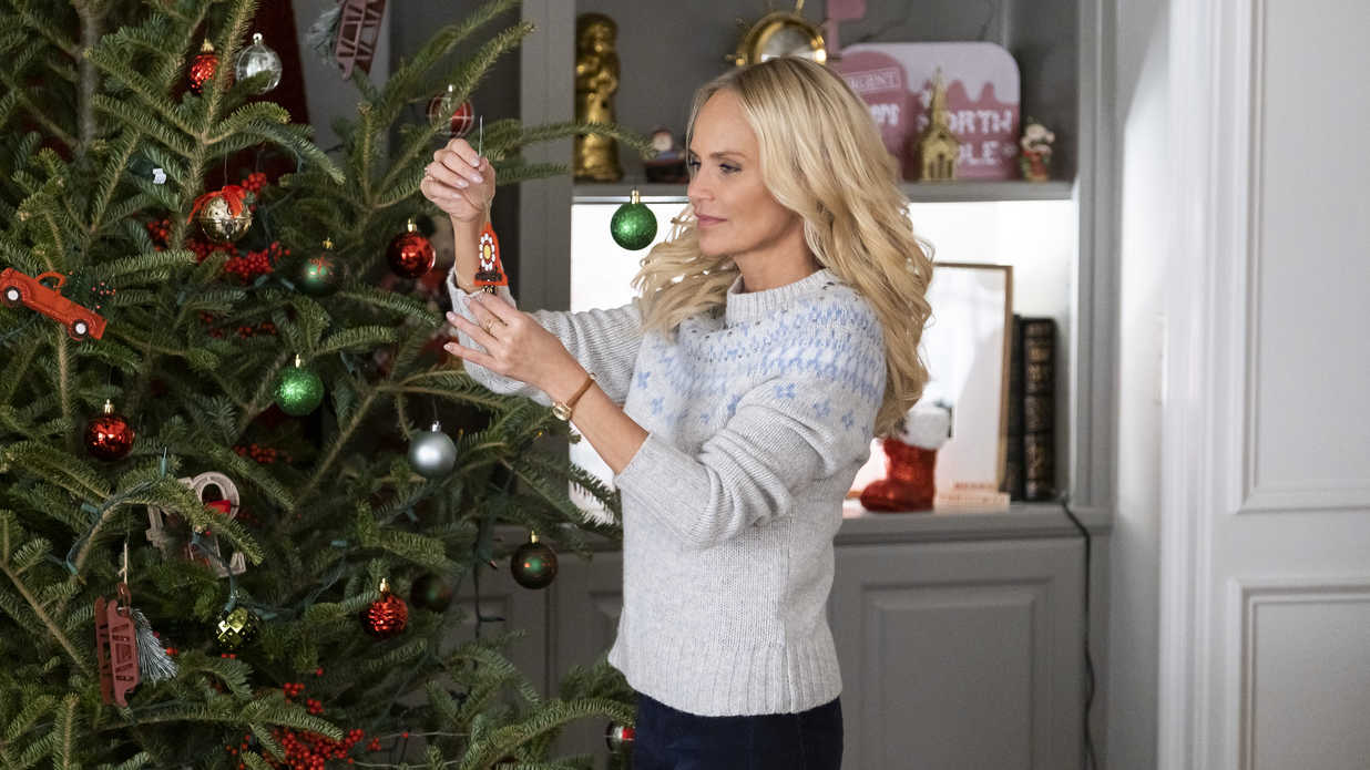 scene from a Christmas movie - woman decorating a Christmas tree