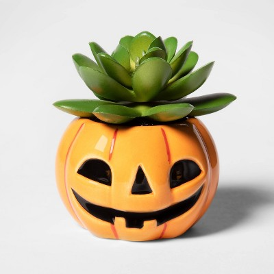 Orange ceramic container decorated like a jack-o-lantern, with a faux succulent inside