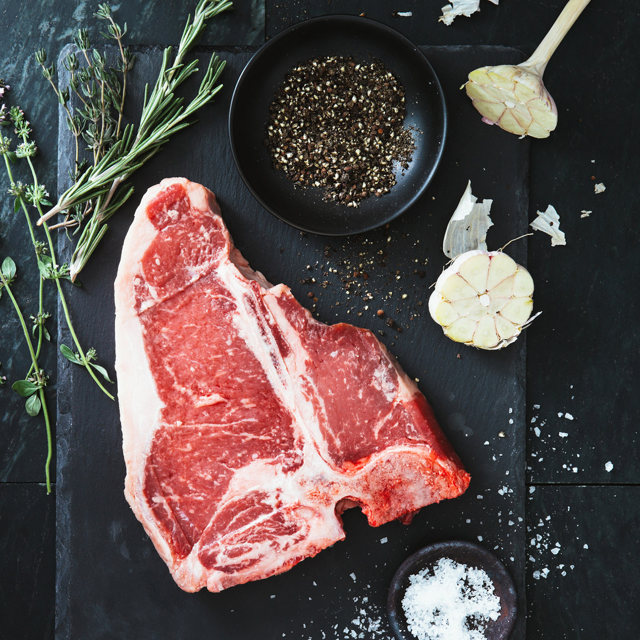 T-Bone steak on a slate serving tray with salt, pepper, garlic and herbs