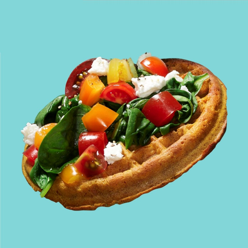 Sauteed Spinach, tomato and feta cheese on top of a frozen waffle