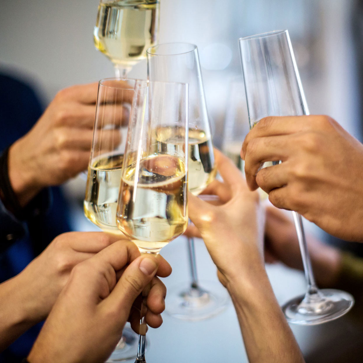 many hands toasting champagne flutes filled with champagne