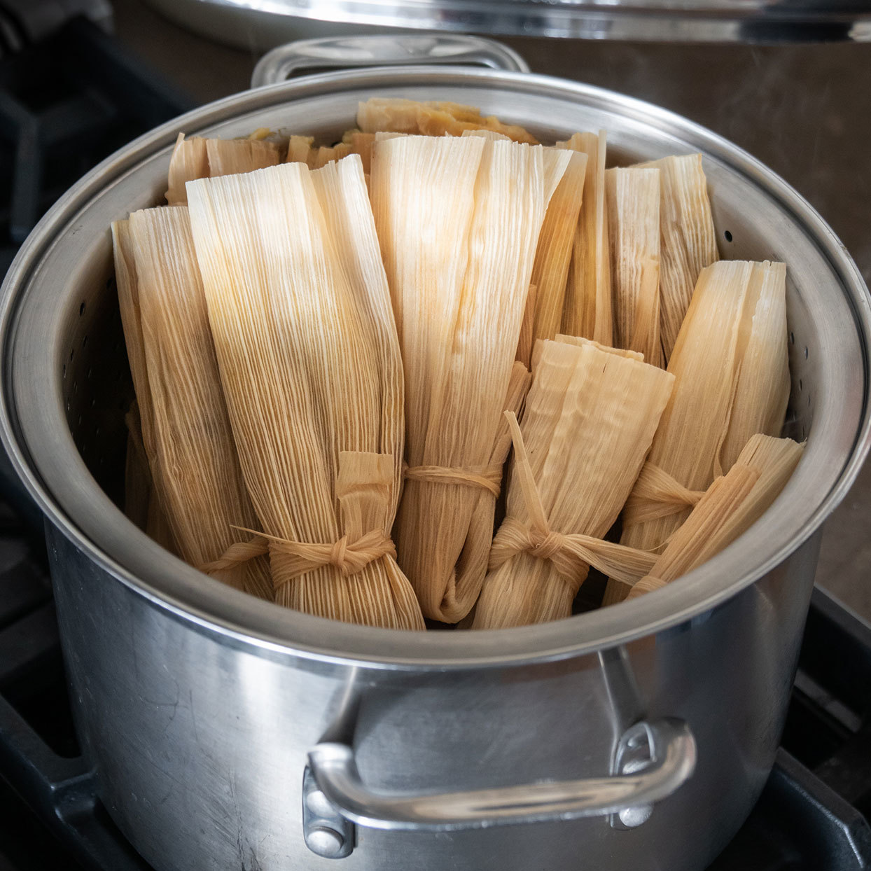 steaming tamales in corn husks in a pot