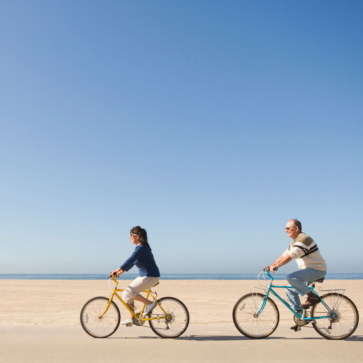 older man and woman riding a bike on a beach