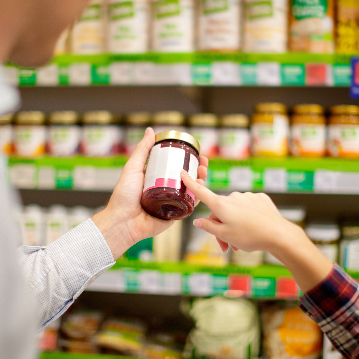people looking at a nutrition label on a jar