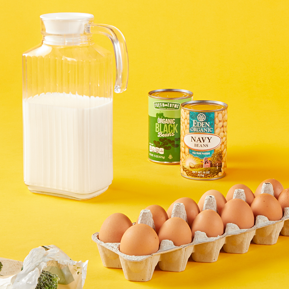 pitcher of milk, 2 cans of beans and a carton of brown eggs