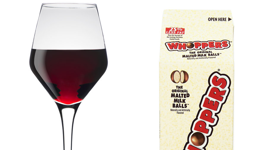 glass of red wine next to a box of Whoppers candy