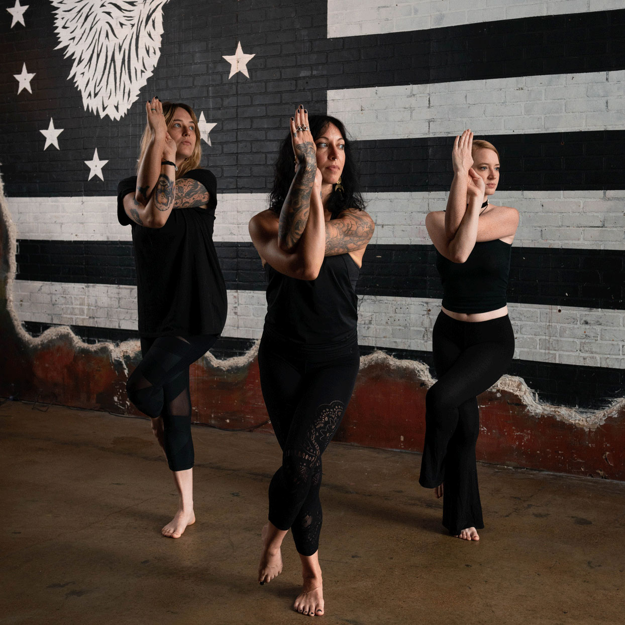 three women in eagle pose - yoga wearing black yoga clothes