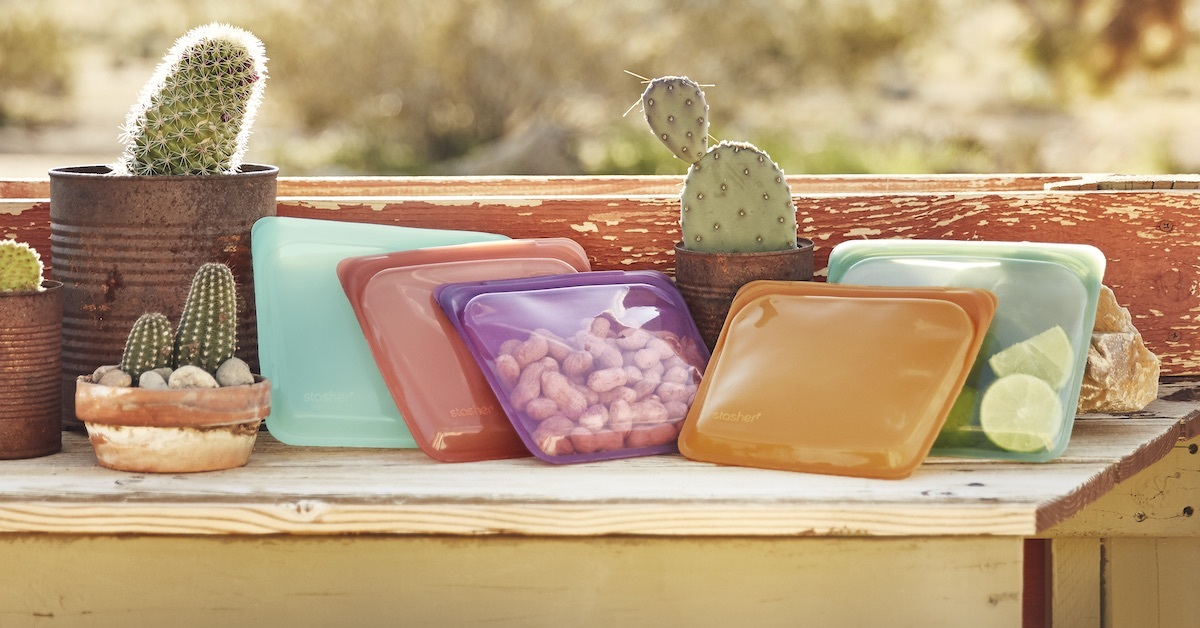 Stasher Bags in different colors sitting on a bench with cacti and a desert background
