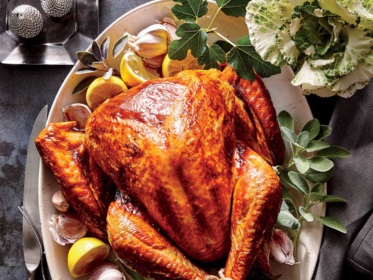 golden brown Tuscan Turkey on a plate with lemon and herb garnishes