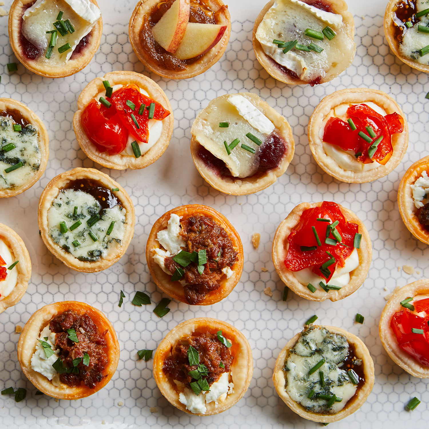 mini appetizer bites lined up on a white surface