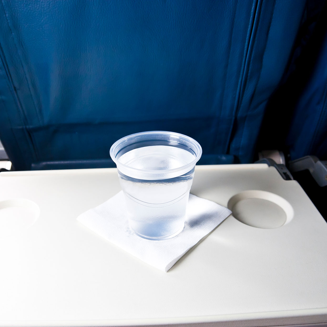 plastic cup of water on an airplane tray