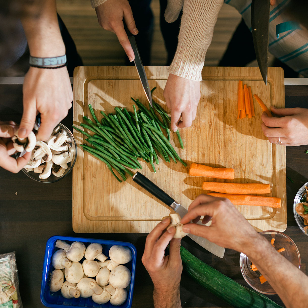 multiple people chopping and prepping various vegetables