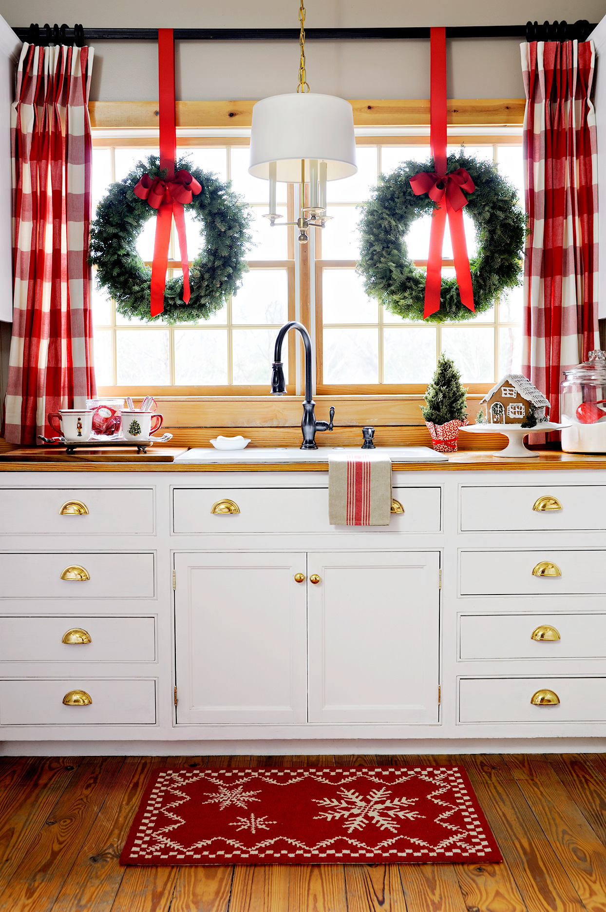 Kitchen decorated with wreaths, red ribbons, red plaid curtains, gingerbread house, and holiday rug