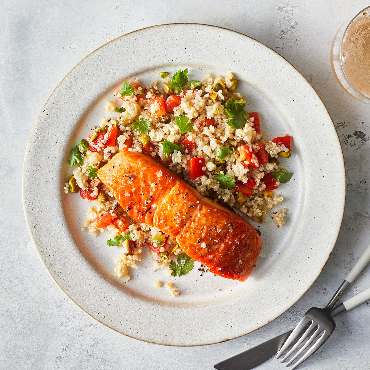 salmon with quinoa salad on a white plate