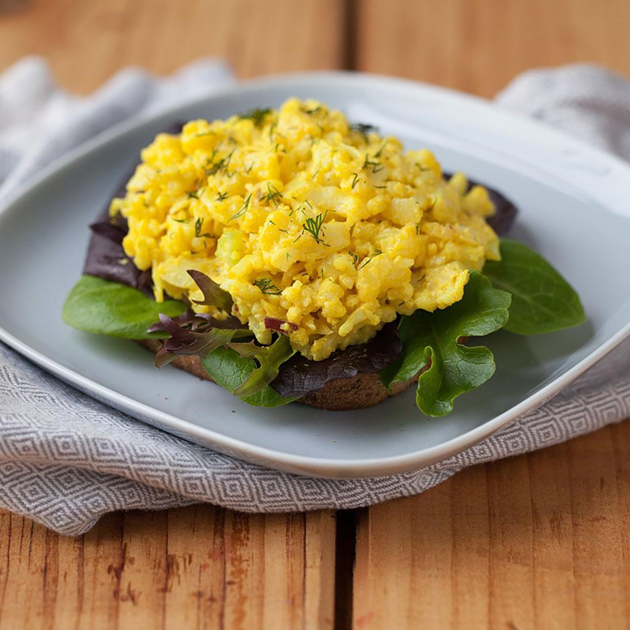 Cauliflower stands in for hard-boiled eggs in this healthy vegan recipe. Serve over a bed of greens or on whole-wheat toast for an easy open-face sandwich.