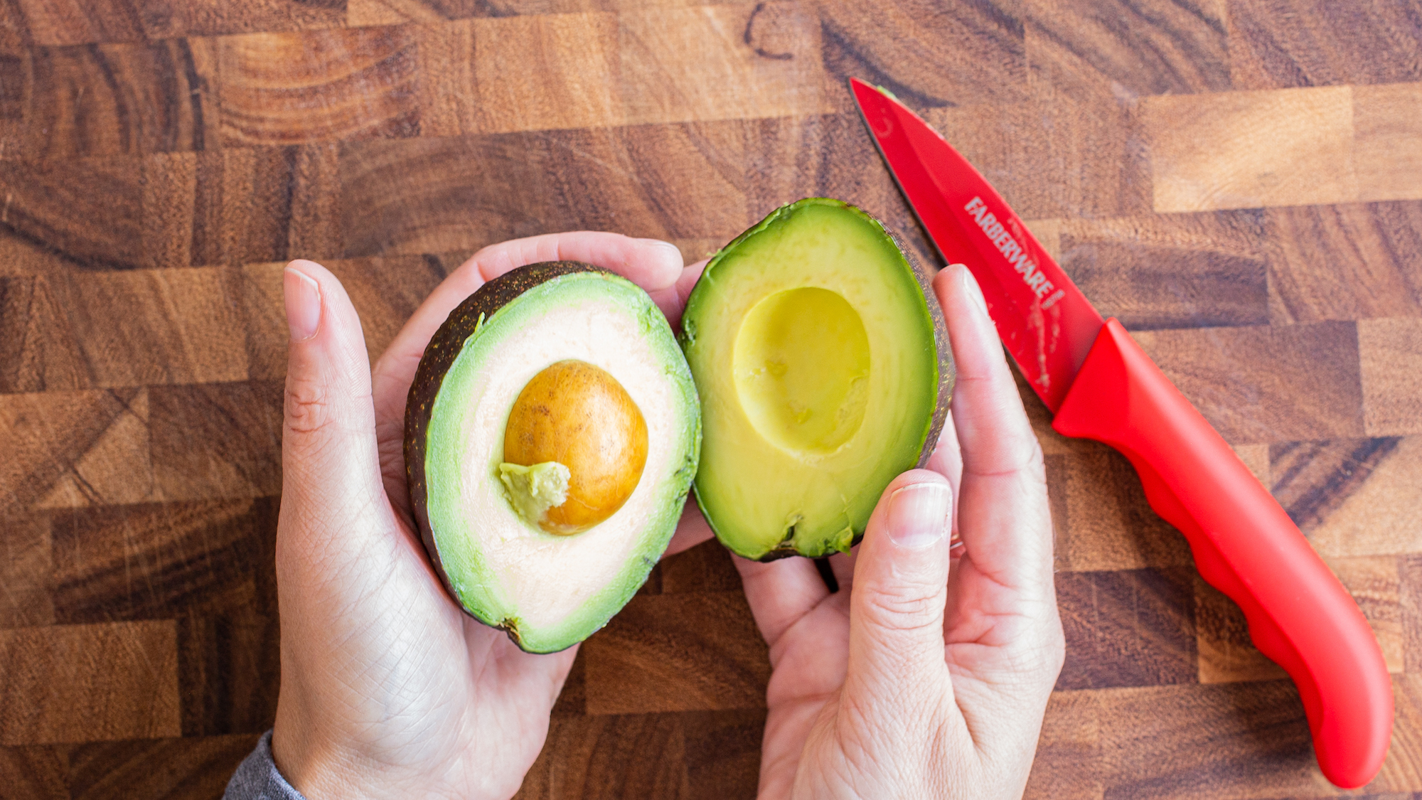 two hands holding avocado halves over a wooden cutting board with red knife