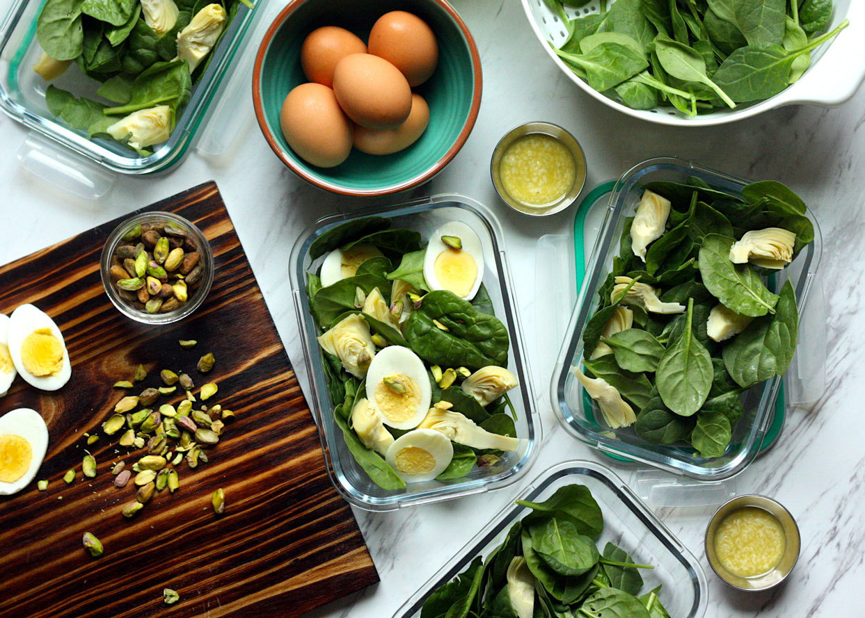 spinach, pistachios, boiled eggs, food containers and dressing ready for food prep
