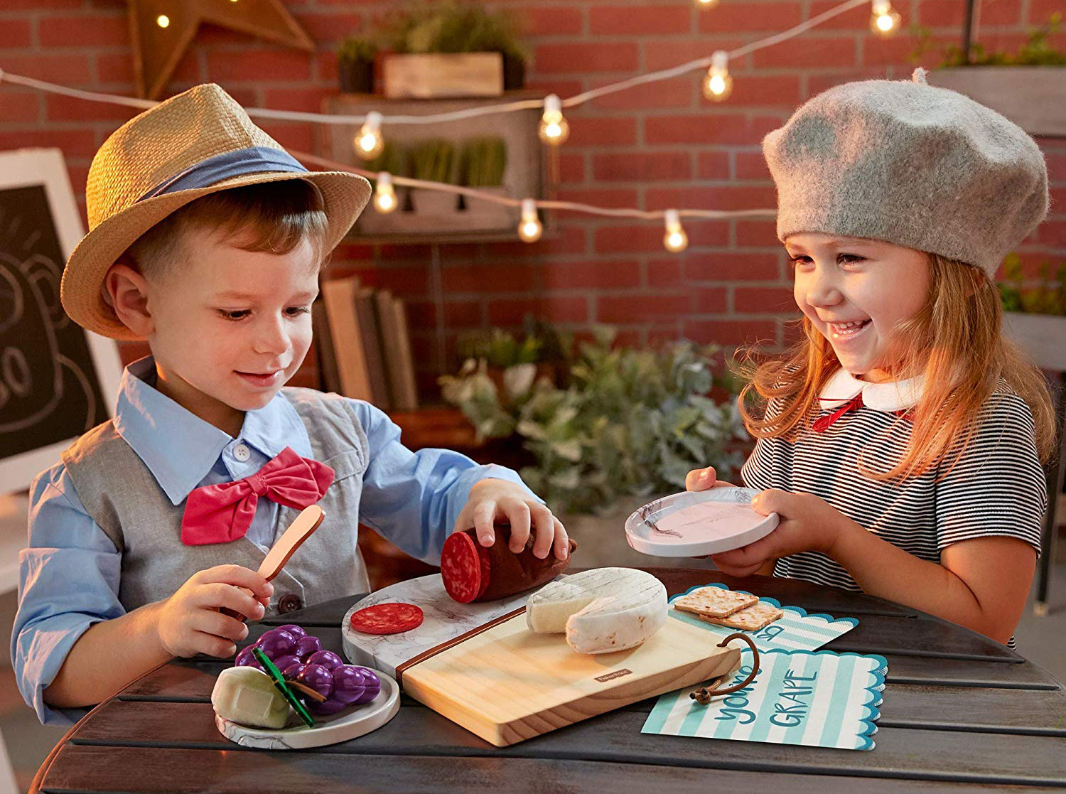 2 children dressed up and playing with a toy charcuterie set
