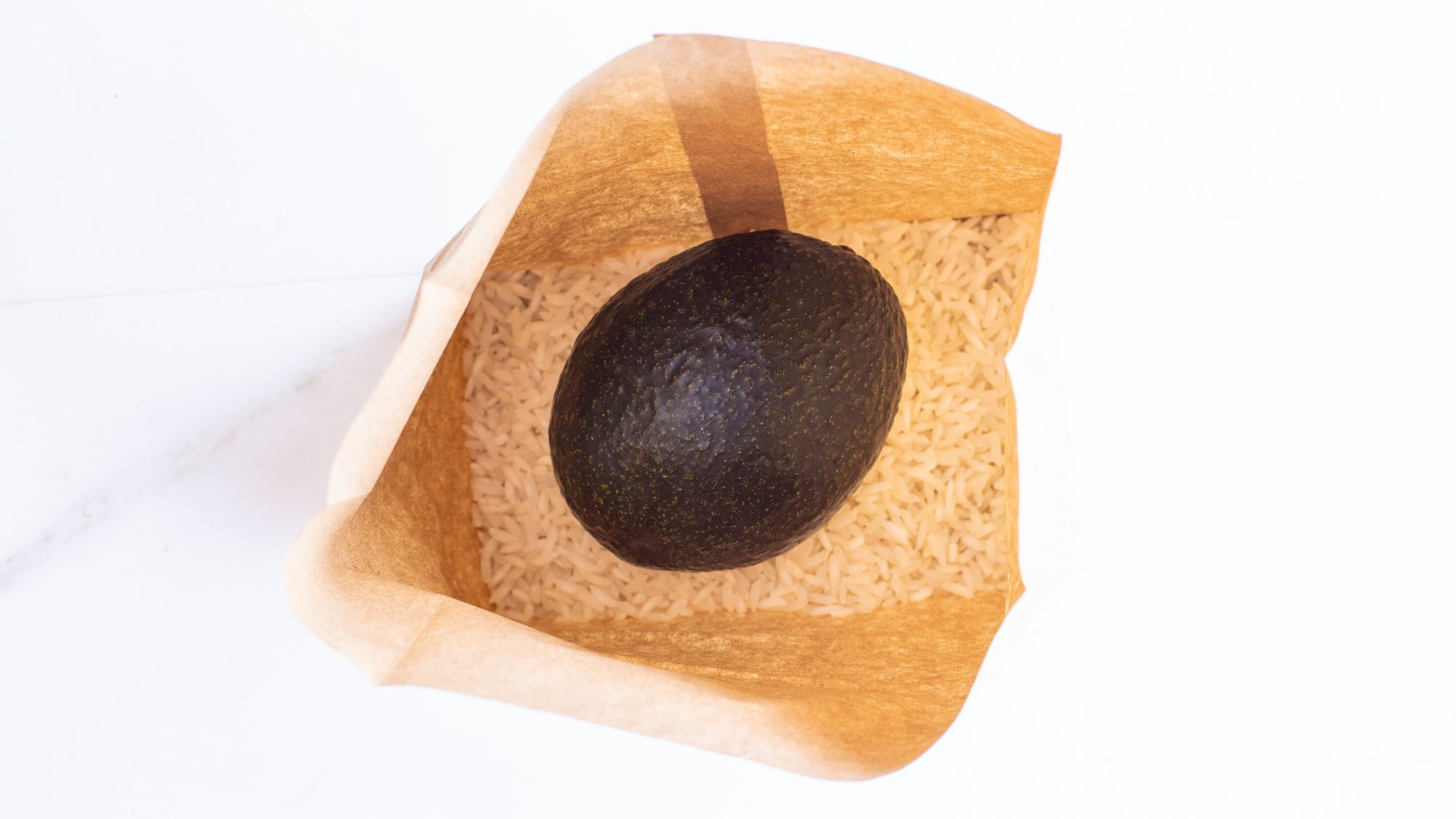 overhead view of avocado in a brown paper bag