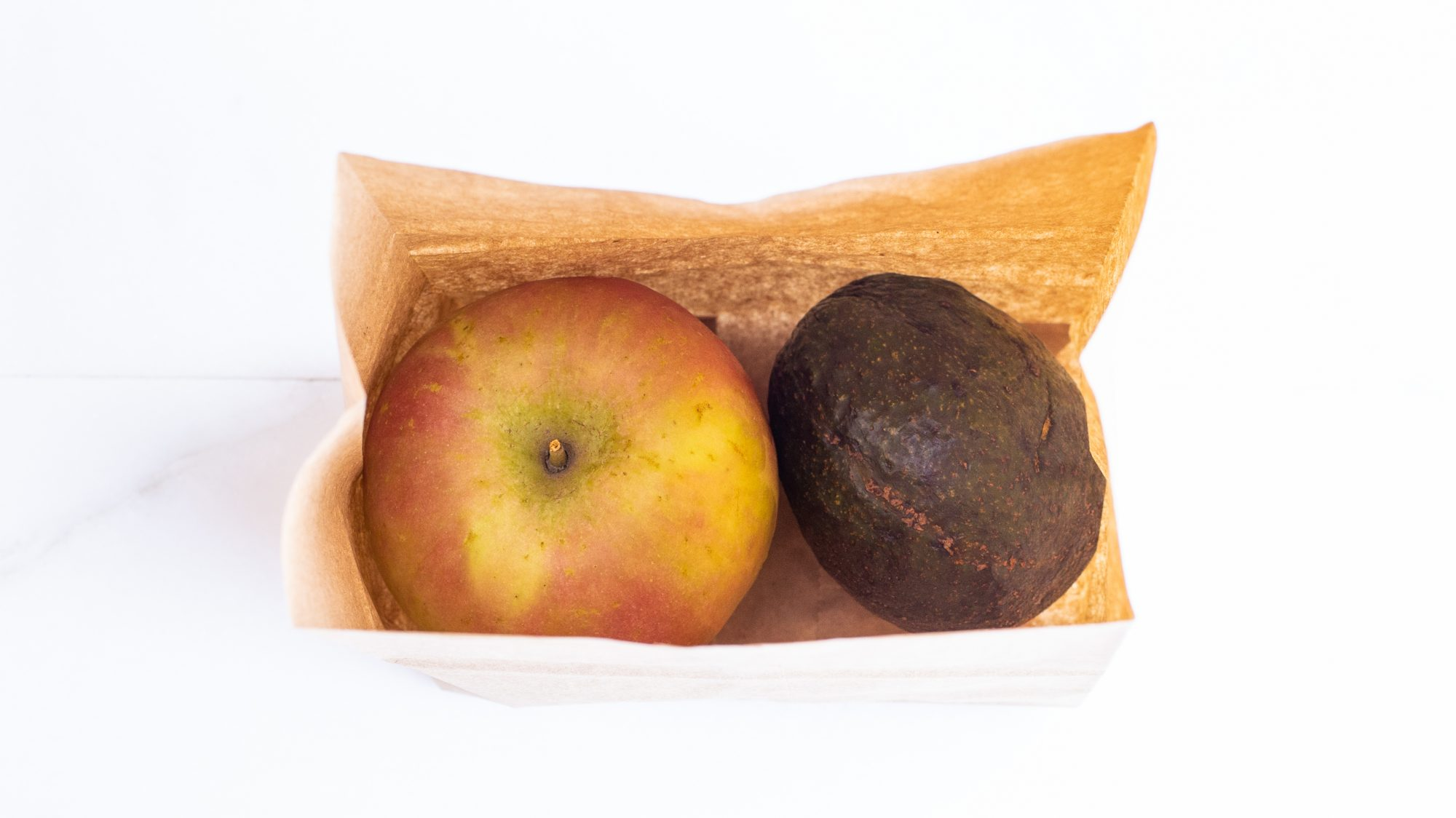 overhead view of avocado and apple in a brown paper bag
