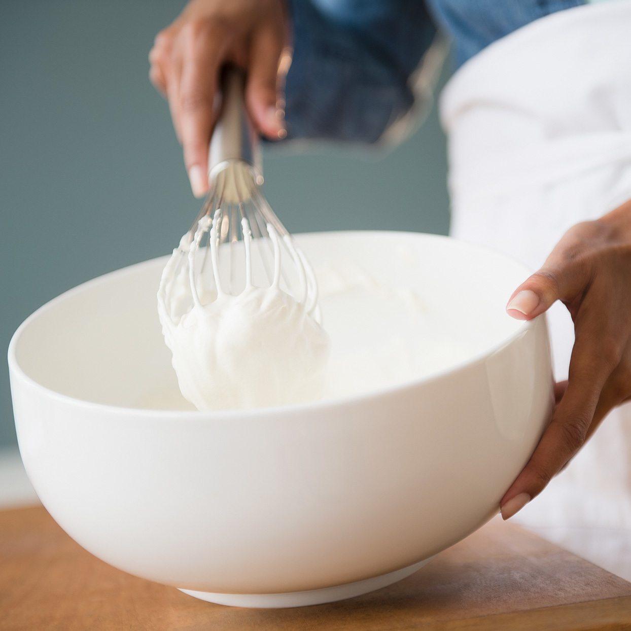 person whipping cream in a bowl with a wisk
