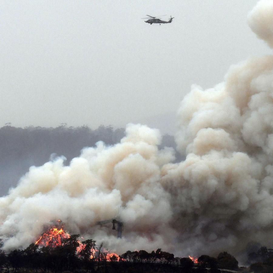 A military helicopter flies above a burning woodchip mill in Eden, in Australia's New South Wales state on January 6, 2020. - January 5 brought milder conditions, including some rainfall in New South Wales and neighbouring Victoria state, but some communities were still under threat from out-of-control blazes, particularly in and around the town of Eden in New South Wales near the Victorian border. (Photo by SAEED KHAN / AFP) (Photo by SAEED KHAN/AFP via Getty Images)