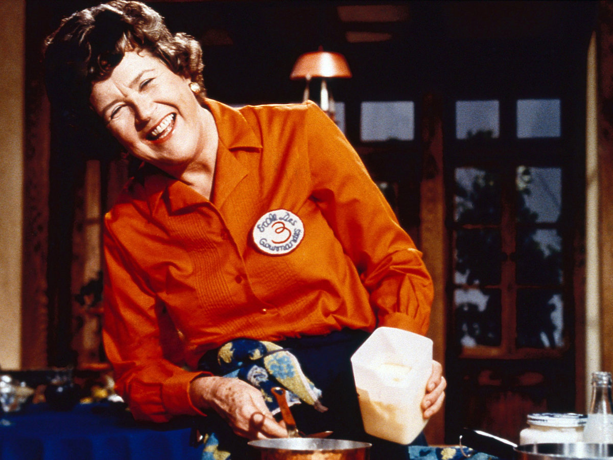 Julia Child smiling and cooking