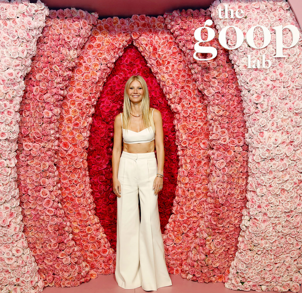"Gwyneth Paltrow standing in front of a flower wall - ""The Goop Lab"""