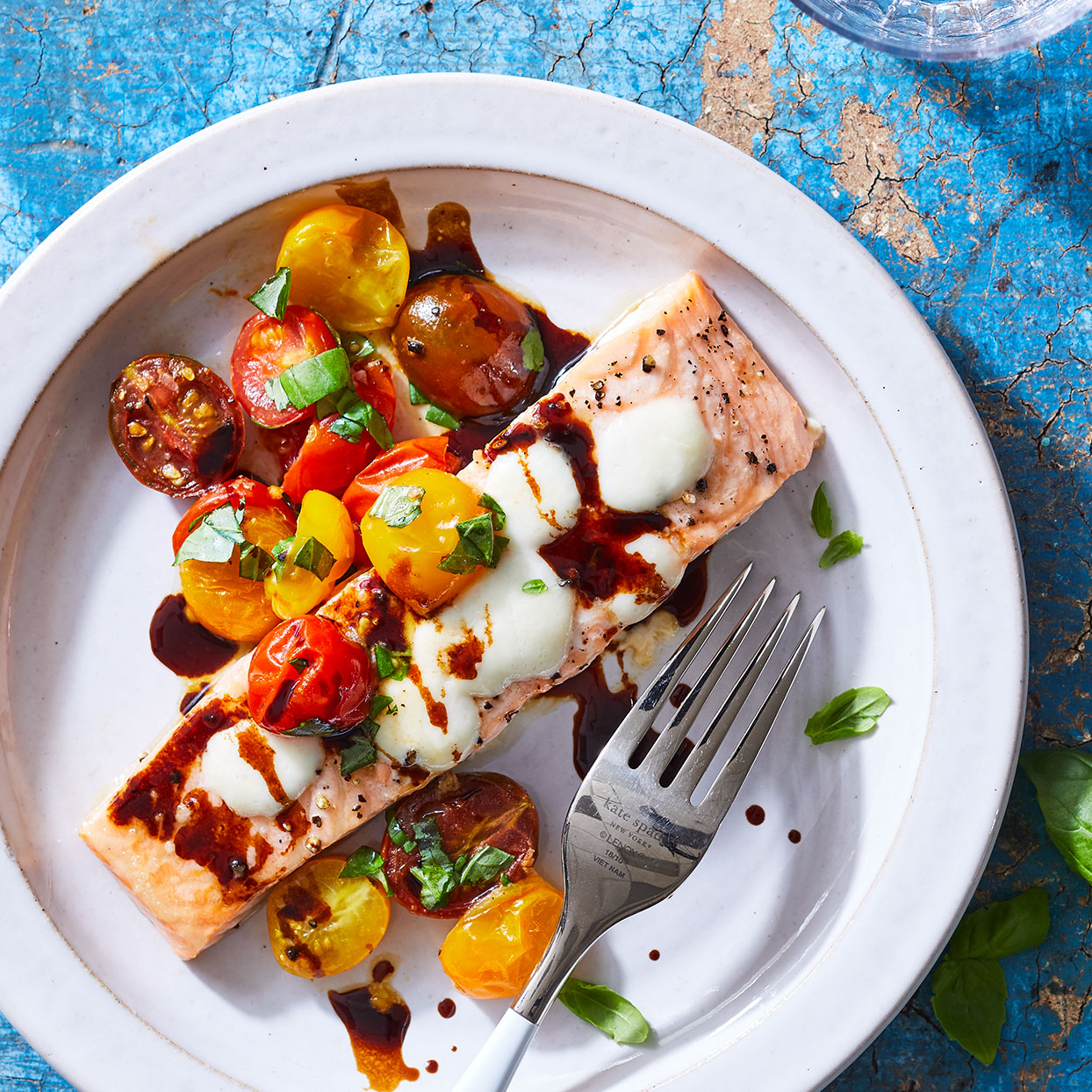 roast salmon with tomatoes and mozzarella on a white plate pictured on a blue background