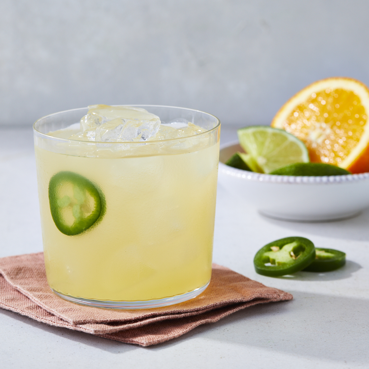margarita in a cocktail glass garnished with jalapeno slices and citrus slices