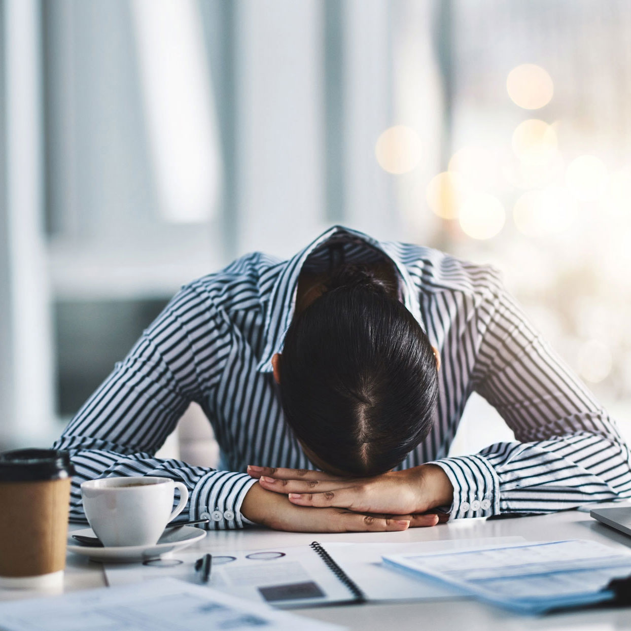 woman with her head down at her desk