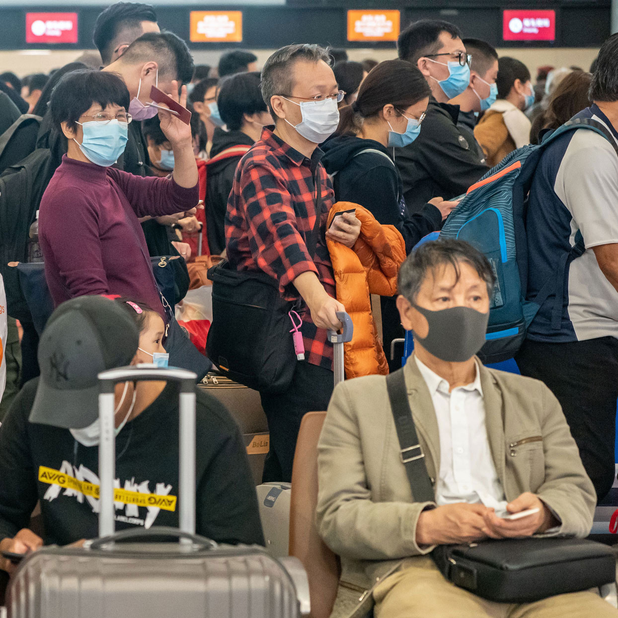 people at an airport wearing medical face masks