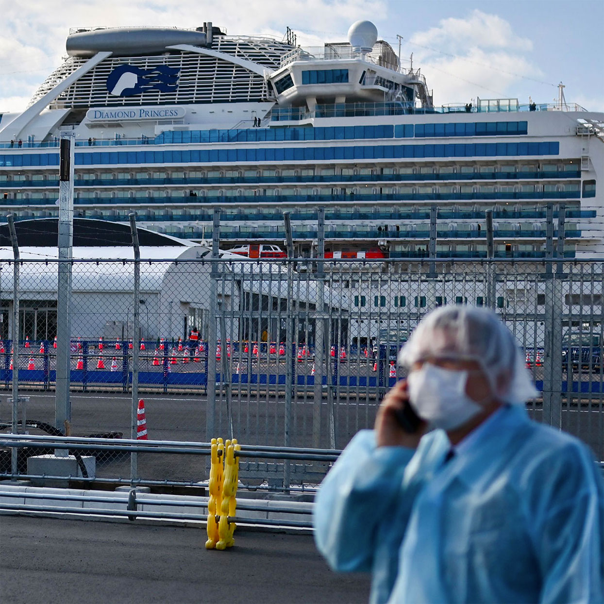 A man in protective gear speaks on the phone near the Diamond Princess cruise ship in quarantine due to fears of the new COVID-19 coronavirus, at the Daikoku Pier Cruise Terminal in Yokohama on February 19, 2020