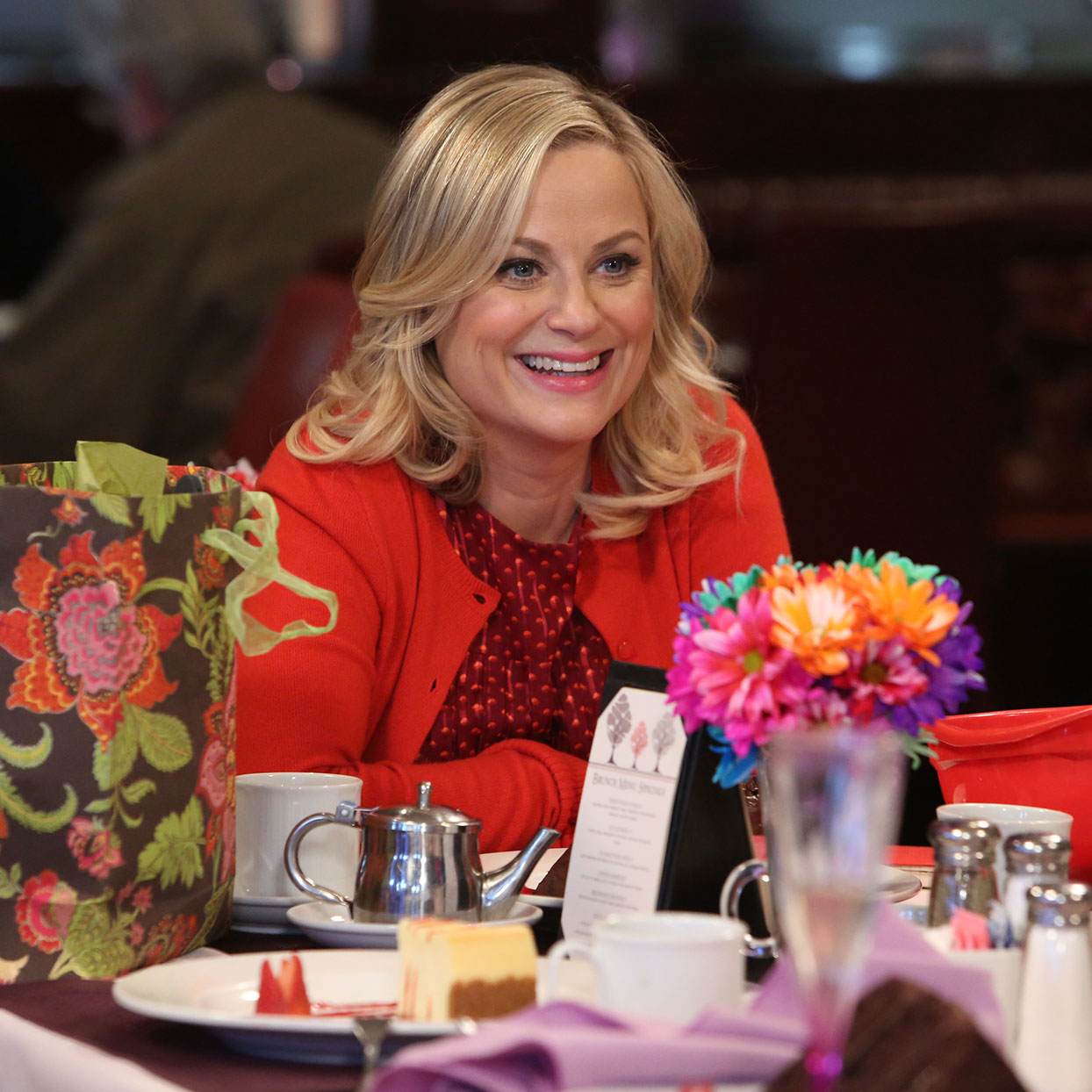 Leslie Knope sitting at a table at a party