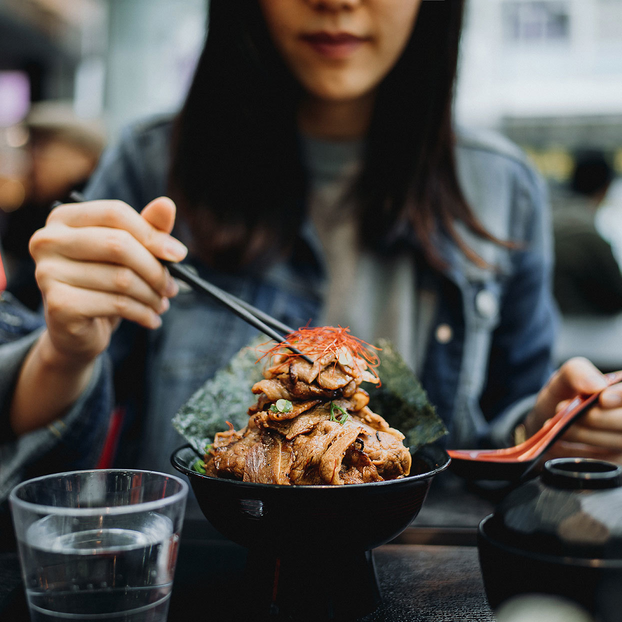 woman eating meat with chopsticks