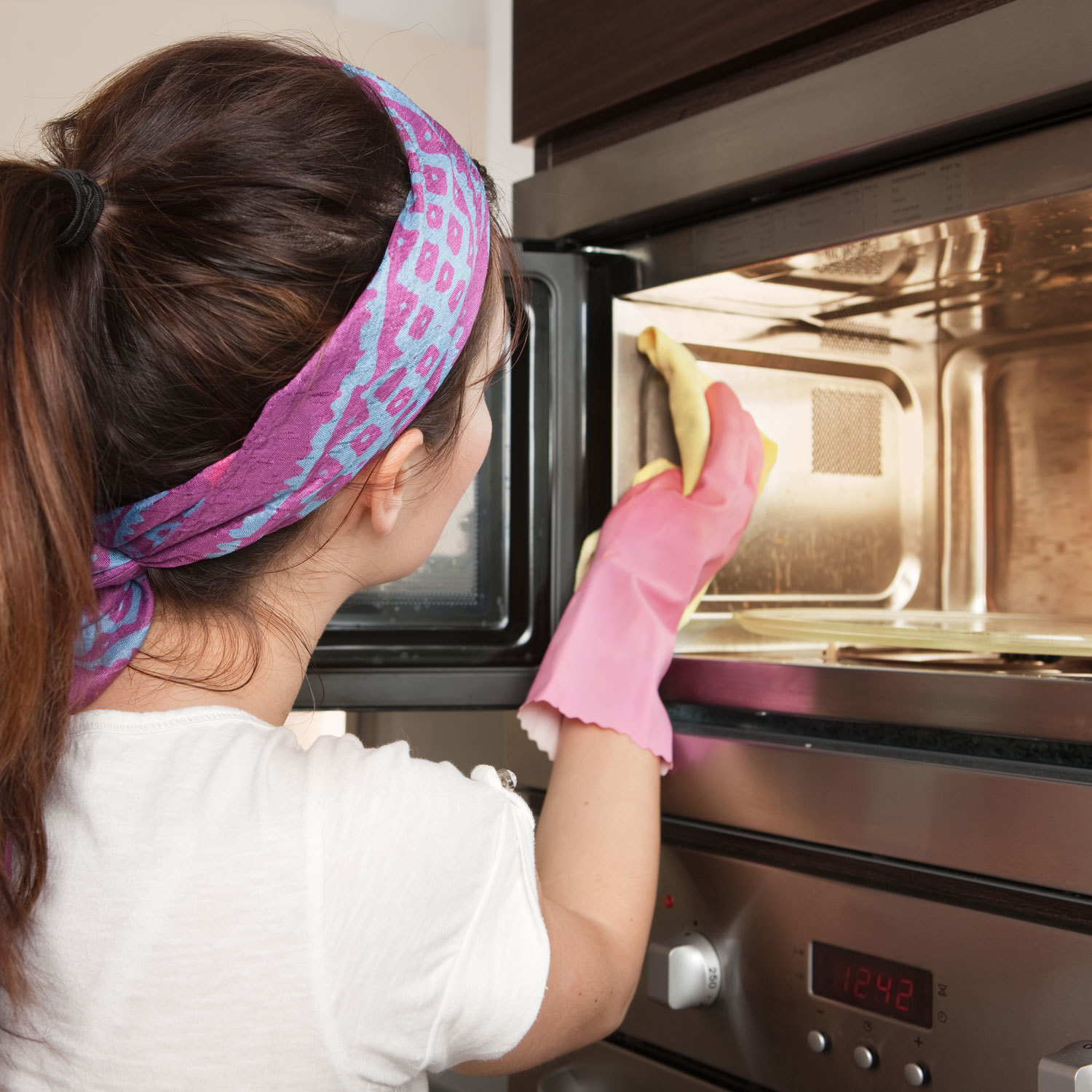 Woman cleaning a microwave oven