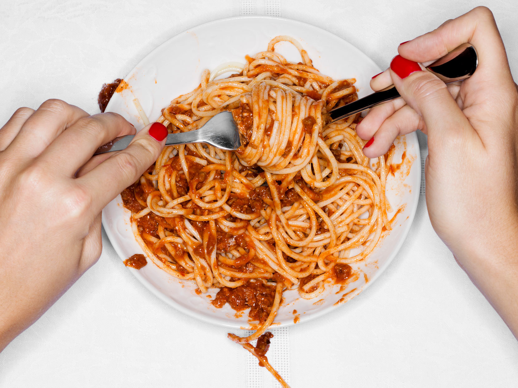 two hands eating plate of spaghetti