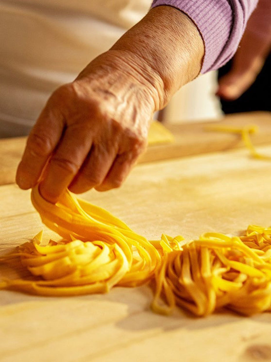 close up of an older woman's hand making pasta