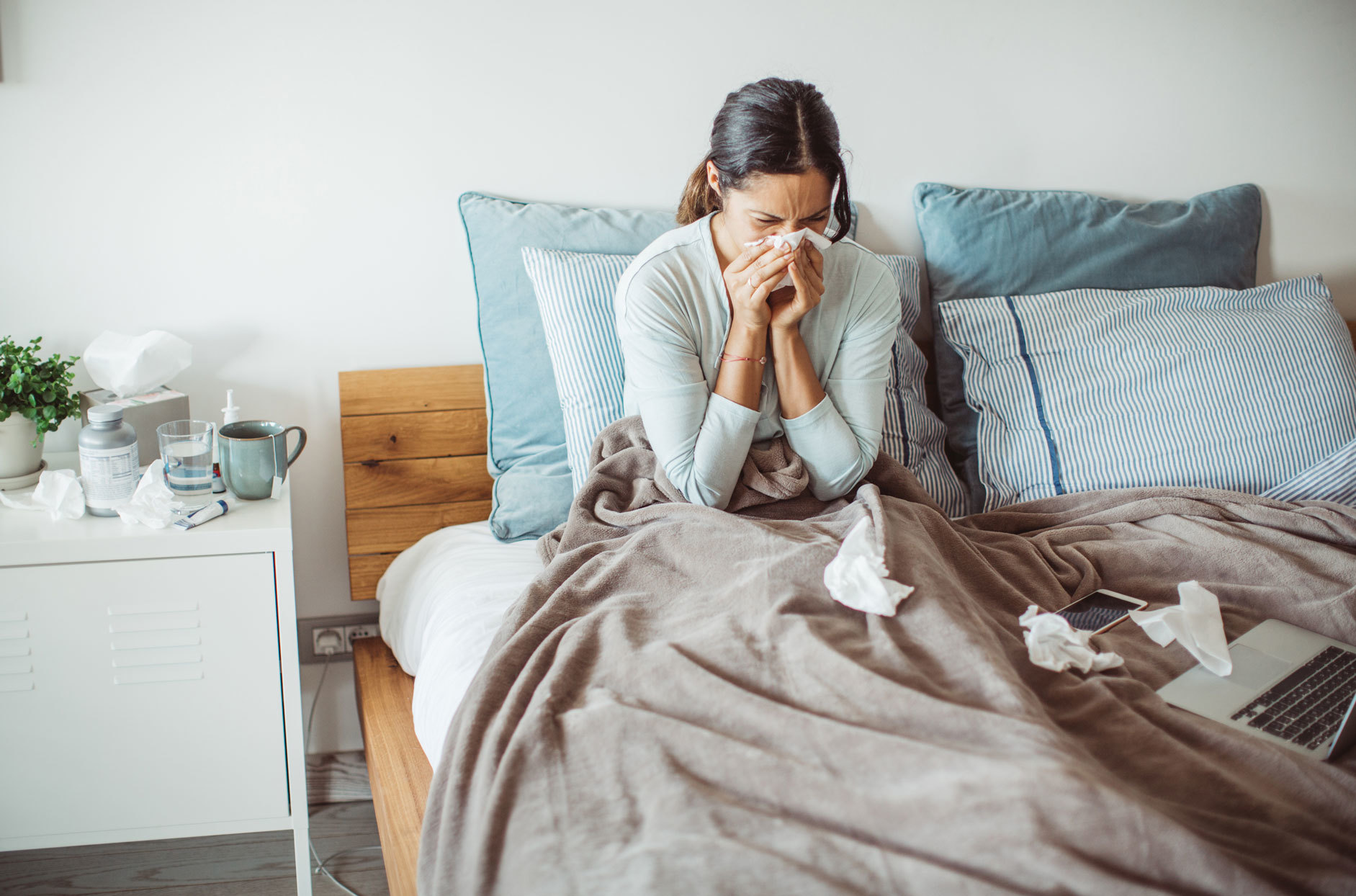 woman in bed sneezing into tissue