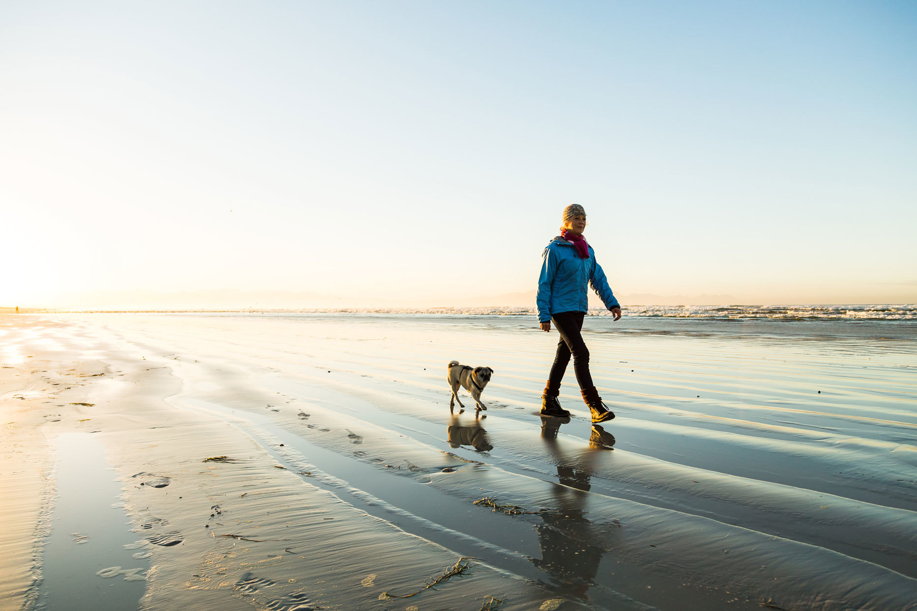 Woman walking on a beach with a dog
